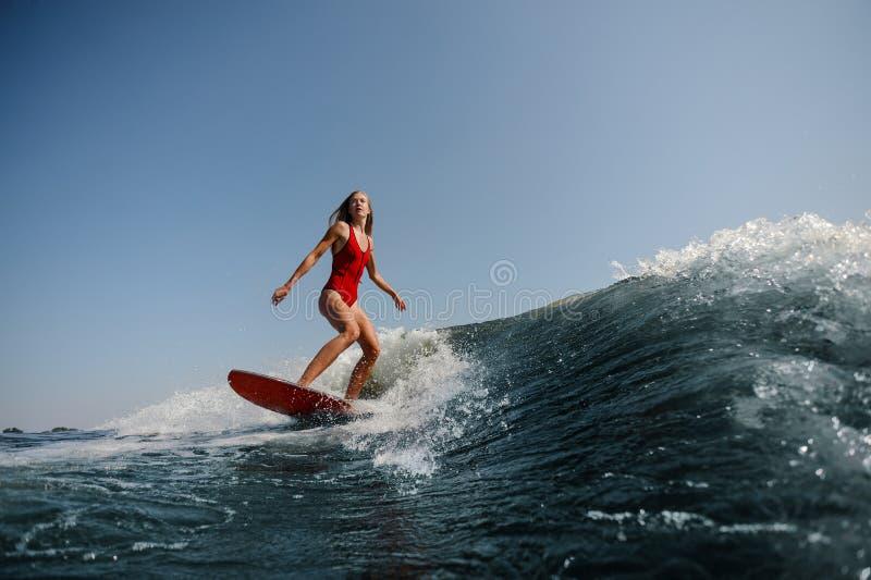 Beautiful slim woman wakesurfing on a high blue wave. Beautiful slim woman in red swimsuit wakesurfing on a high blue wave on warm sunny day royalty free stock photography