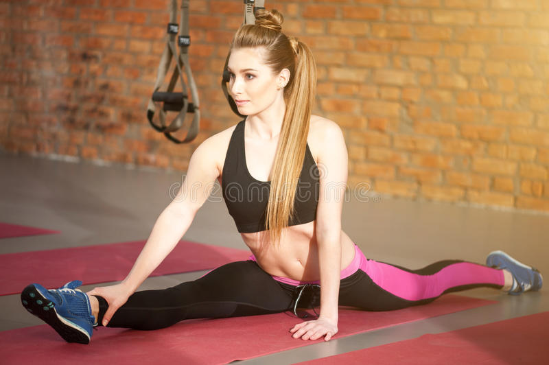 Beautiful slim woman sitting on the string. Cheerful young girl is doing splits on flooring in gym. She is looking forward with confidence royalty free stock photos