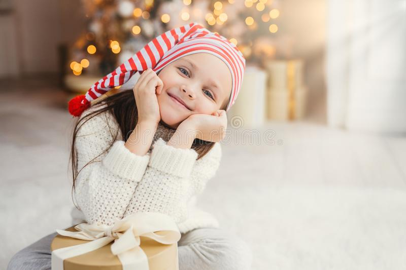 Beautiful small child poses in living room, leans at present gift, has happy expression, glad to recieve surprise from parents, sp stock photography