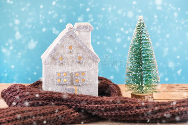 Christmas toy house wrapped in warm scarf and green Xmas tree stock images