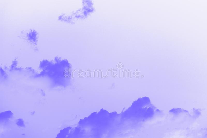 Beautiful small fluffy clouds on a sky background. Copy space. Purple violet toned stock photography