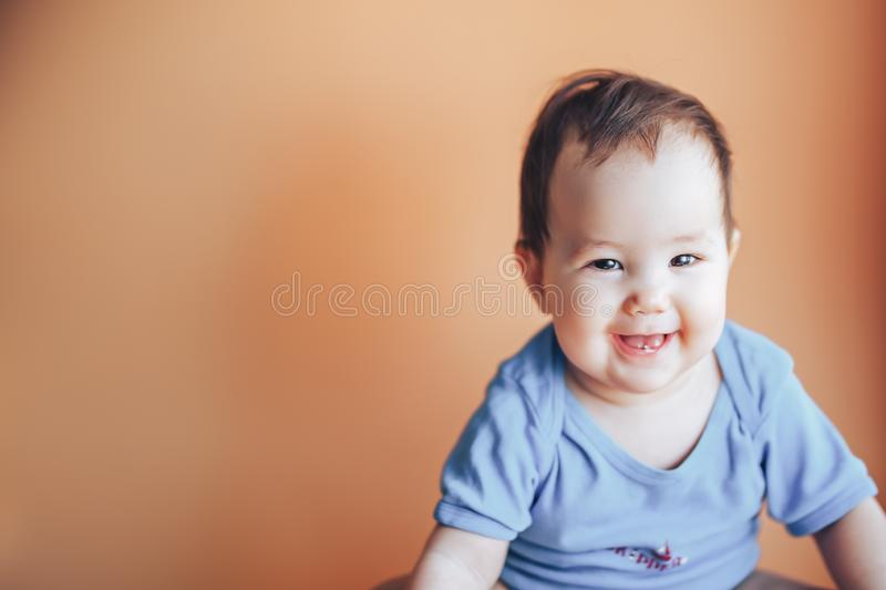 Beautiful small girl or boy with dark hair smiling on a bright orange background colour of 2019 with space for text happy smile. Look at camera stock photo