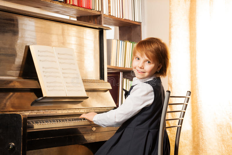 Beautiful small girl with short hair playing piano stock images