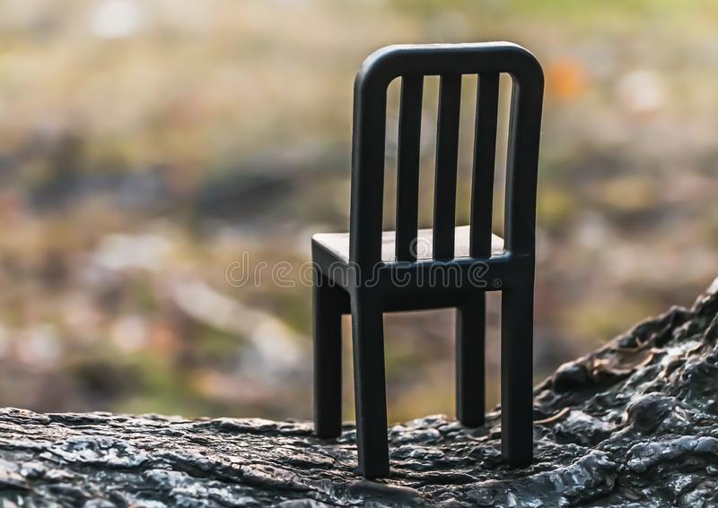 A beautiful small toy black plastic chair is on a blurred background. In the park stock images