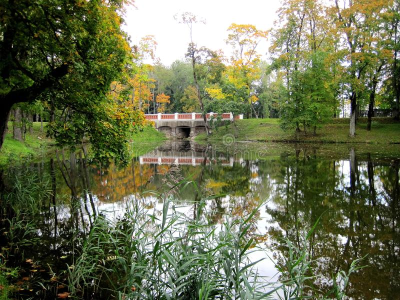 Small bridge and trees in park, Lithuania. Beautiful small walking bridge, lake and nice trees in autumn in Plunge town park stock image