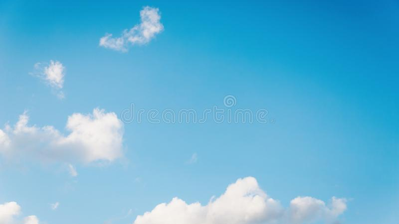 Beautiful small white fluffy clouds on a blue sky background. Copy space, 16:9 panoramic format. Beautiful small white fluffy clouds on a light blue sky royalty free stock photography