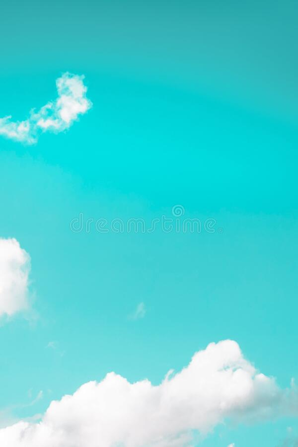 Small white fluffy clouds on a mint aqua menthe background. Copy space. Beautiful small white fluffy clouds on a mint aqua menthe background. Copy space stock photography
