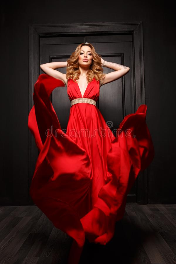 Beautiful smart dressed woman in the red evening fluttering dress is flowing and posing in move. The wooden door is on the background. Indoor stock photo