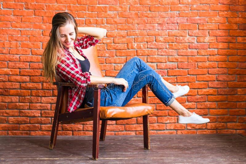 Beautiful smart woman sits on chair near brick wall royalty free stock photos