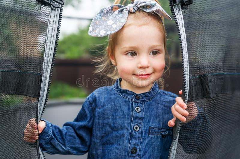 Beautiful smile little girl is in the playground. Little girl with bow looking through net on trampoline stock image