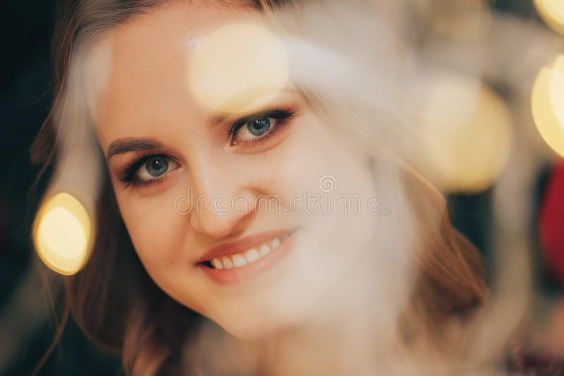 Beautiful smiles woman looking at the camera through the lights of the garland royalty free stock image