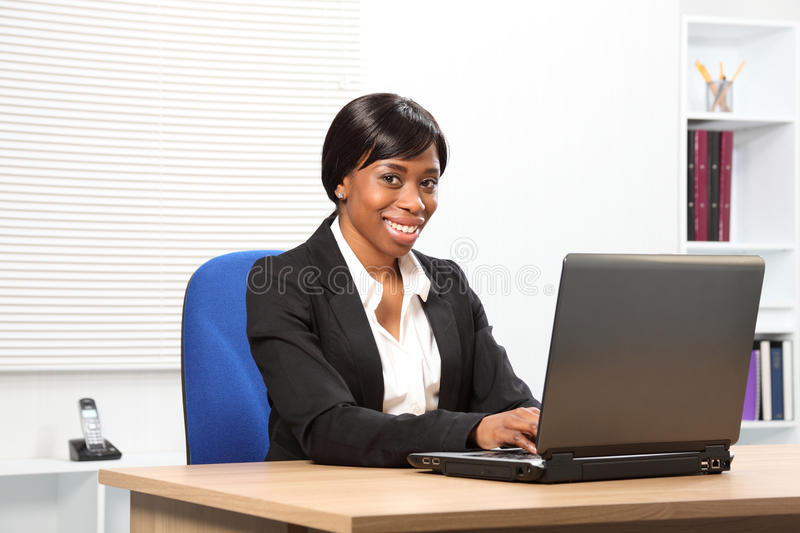 Beautiful smiling african american business woman. Beautiful young African American woman working in office looking up from her laptop with a lovely smile stock image
