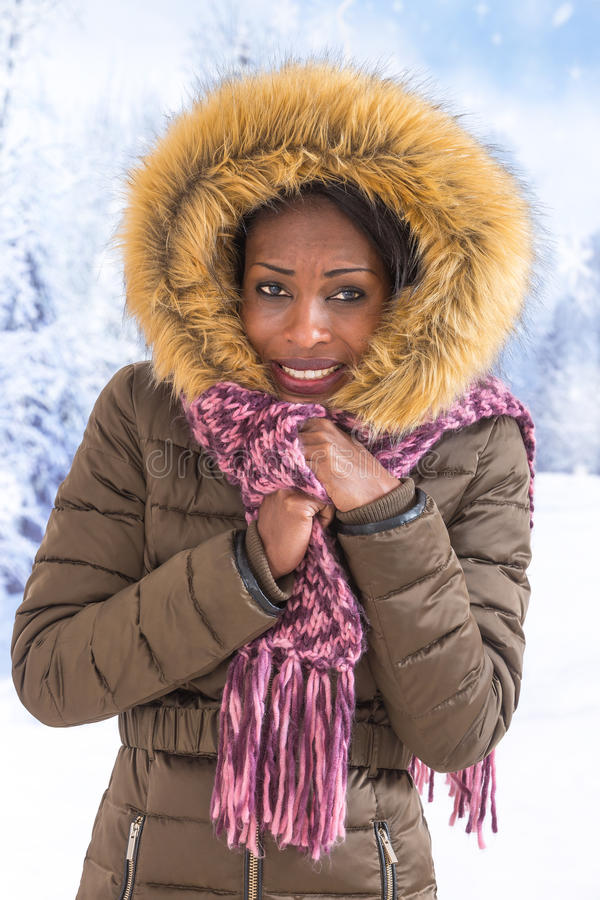 Beautiful smiling African woman wearing a fur coat and hood over snow in winter day royalty free stock photos