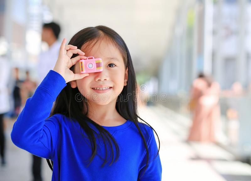 Beautiful smiling Asian little girl taking photo by toy camera to take pictures outdoor. Kid development concept royalty free stock photo