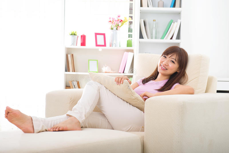Beautiful smiling Asian woman with tablet computer. Lying on sofa royalty free stock photo