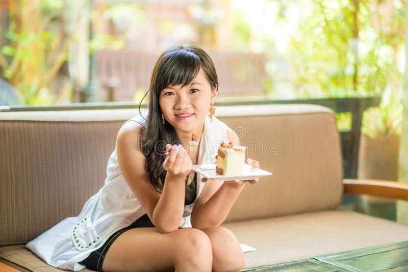 Beautiful smiling asian young woman sitting on sofa stock photo