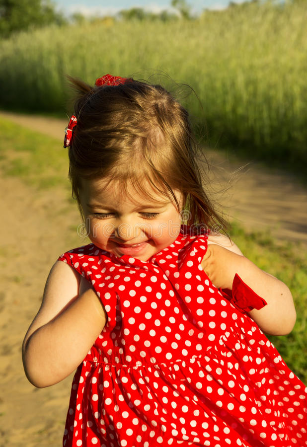 Beautiful smiling baby girl in red dress in summer day royalty free stock photo