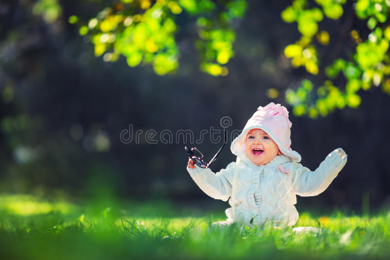 Beautiful smiling baby girl sitting on green grass royalty free stock image