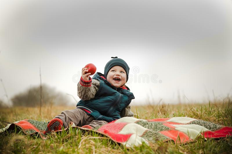 The child laughs at a picnic and eats a delicious apple stock image