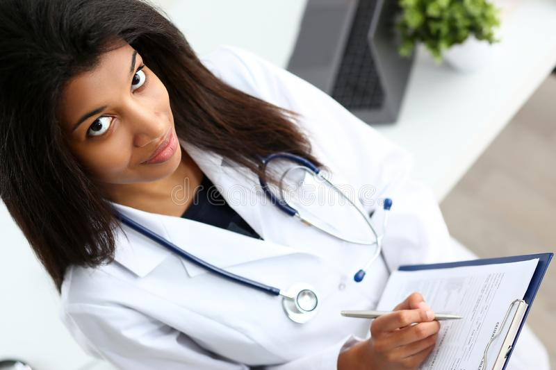 Beautiful smiling female doctor hold. Beautiful smiling black female doctor hold clipboard pad and fill something with silver pen. Physical illness prevention stock photos