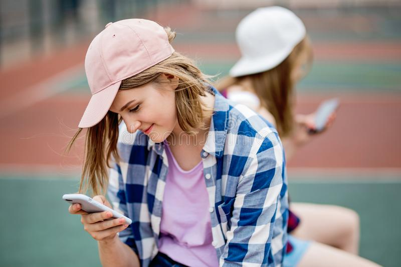 A beautiful smiling blond girl wearing checkered shirt and a cap is sitting on the sports field with a phone in her hand royalty free stock photo