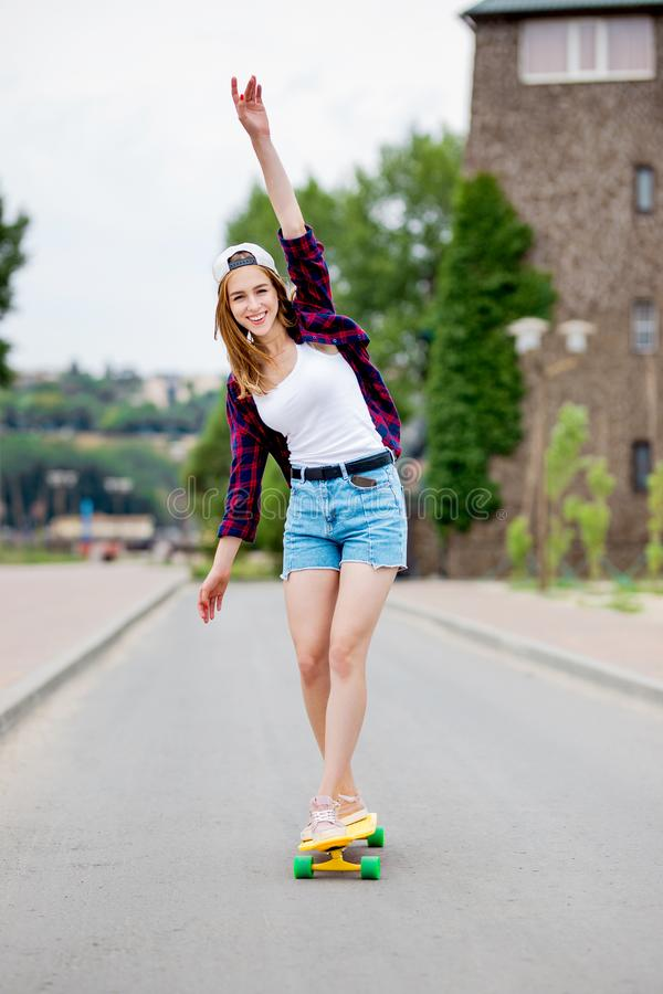 A beautiful smiling blond girl wearing checkered shirt, white cap and denim shorts is balancing on the yellow longboard stock photos