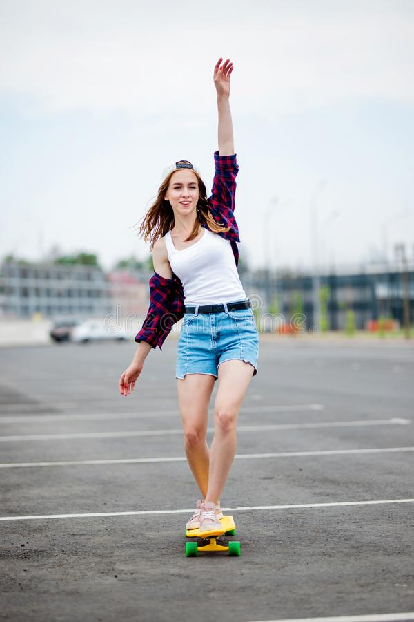A beautiful smiling blond girl wearing checkered shirt, white cap and denim shorts is balancing on the yellow longboard royalty free stock images