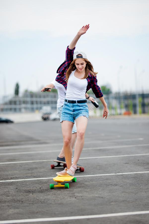 A beautiful smiling blond girl wearing checkered shirt, white cap and denim shorts is balancing on the yellow longboard royalty free stock image
