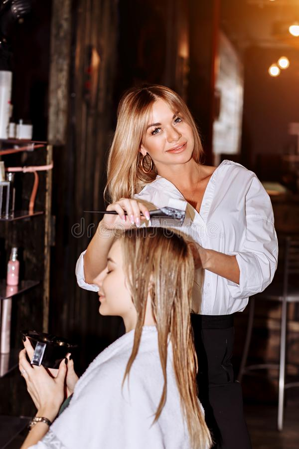 Beautiful smiling blond hairstylist with her client in hairdresser. Care, profession, cosmetology, spa, beauty salon. Concepts stock photo