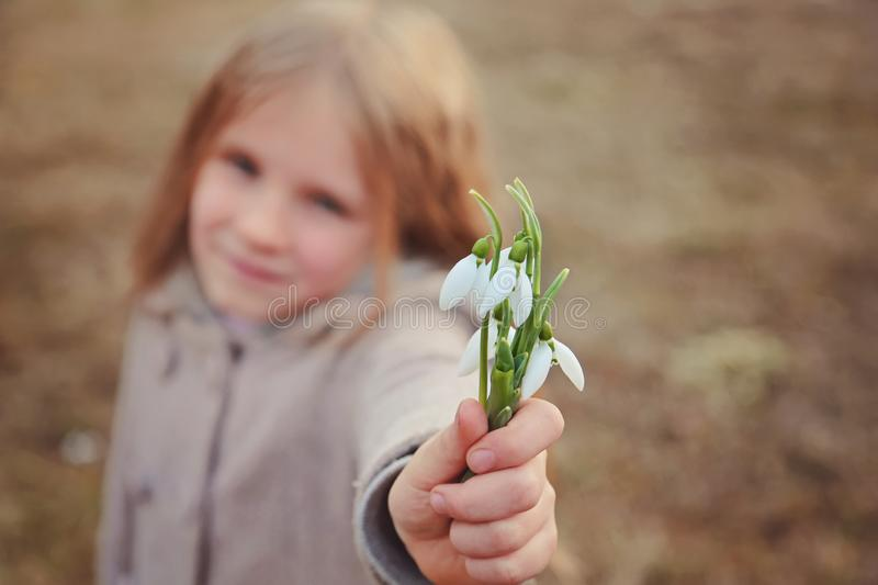 Beautiful smiling blond with long hair little girl with bouquet of first spring flowers snowdrops. Girl holds flowers and smiling stock photos