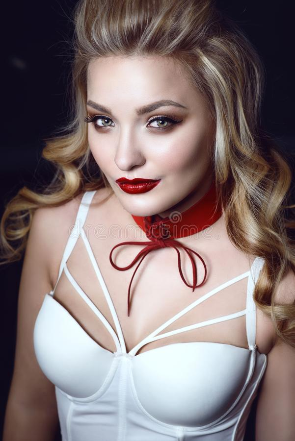 Beautiful smiling blond model with perfect make up and scrapped back hair wearing white corset strapped top and red choker stock images