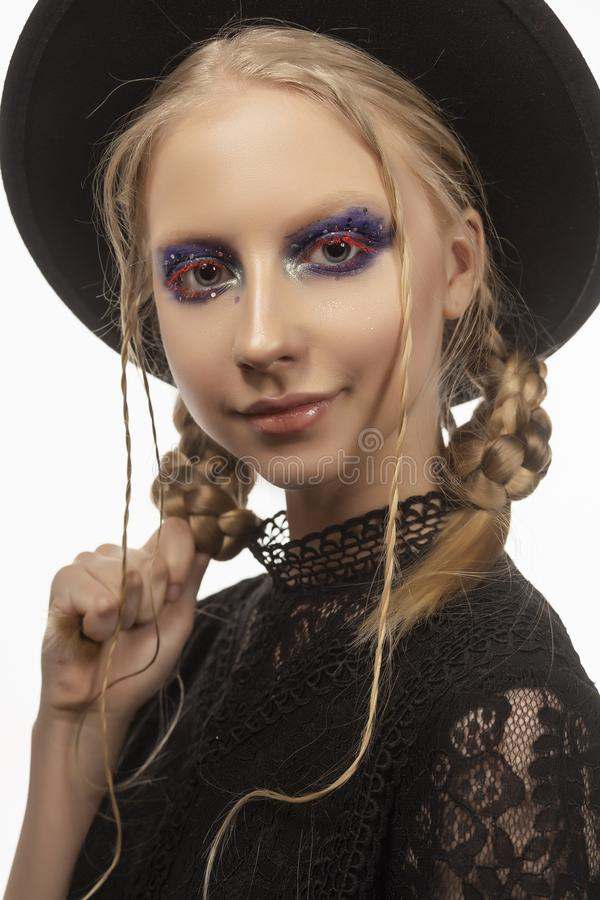 A beautiful smiling blond teenage girl wearing a black witch got stock photos
