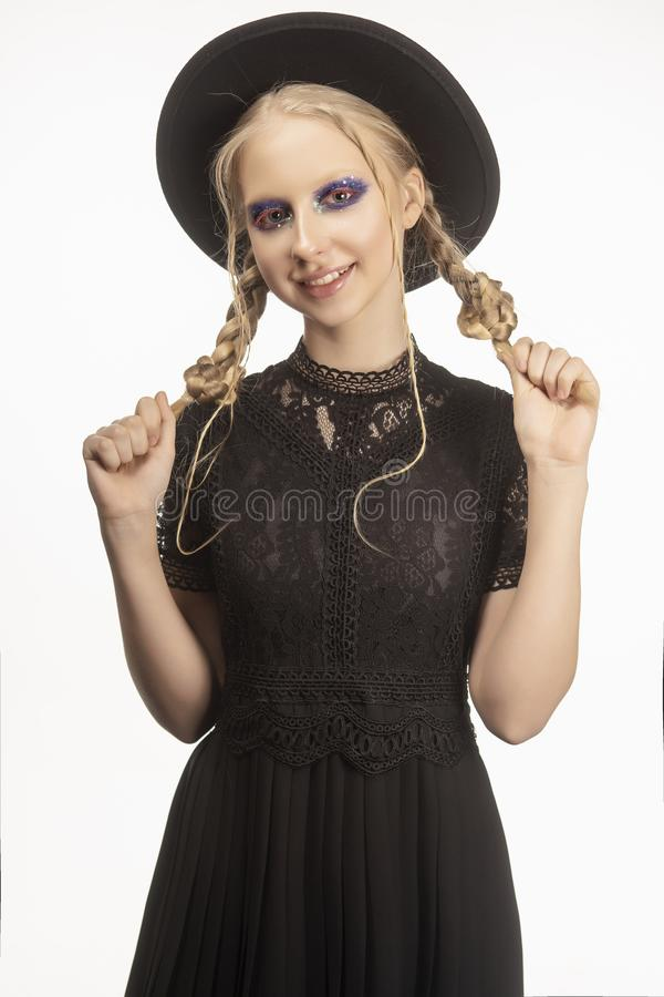 A beautiful smiling blond teenage girl wearing a black witch got royalty free stock images