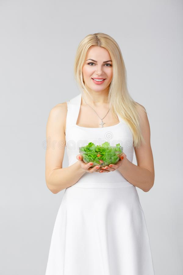 Woman in white dress with fresh salad royalty free stock images