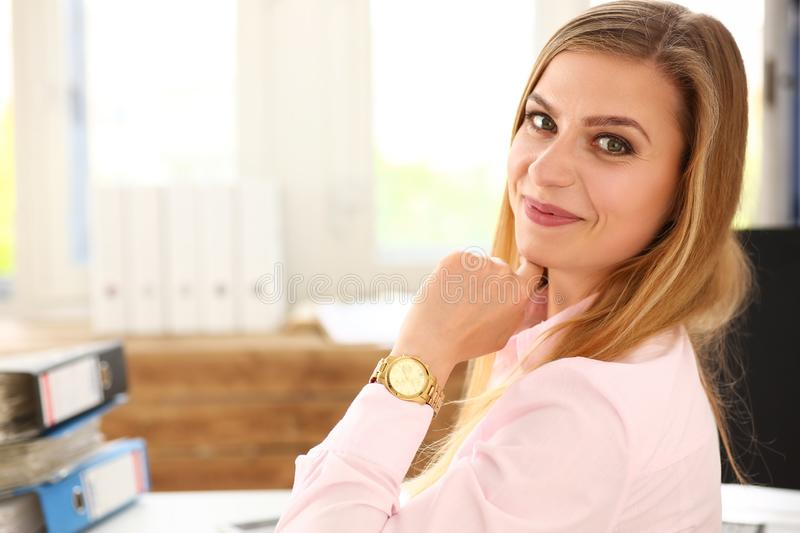 Beautiful smiling blonde clerk woman sitting at working table royalty free stock images