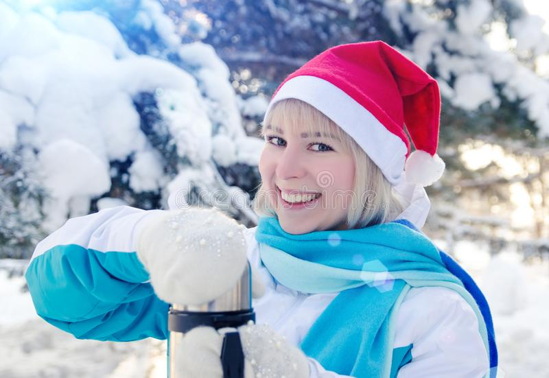 Beautiful smiling blonde girl in a red Christmas hat opens a thermos with hot tea.  royalty free stock photo