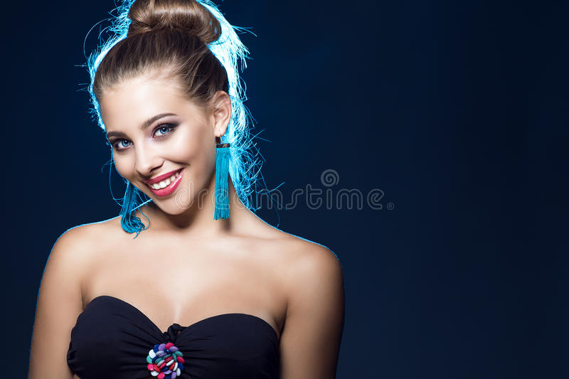 Download Beautiful Smiling Blue-eyed Young Girl With Perfect Make Up Wearing Black Strapless Bra And Blue Tassel Earrings Stock Image - Image of beautiful, female: 97486373