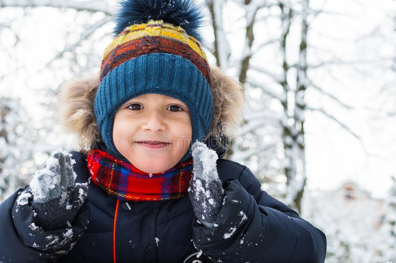 Beautiful smiling boy 5 years old in winter in outdoors royalty free stock photography