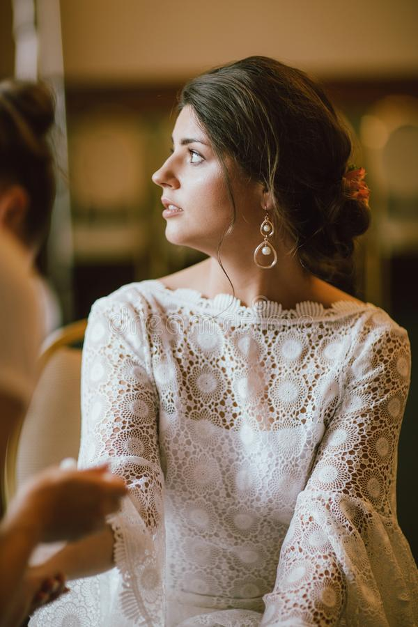 Beautiful smiling bride brunette young woman in white lace dress near window, bridal morning stock photo