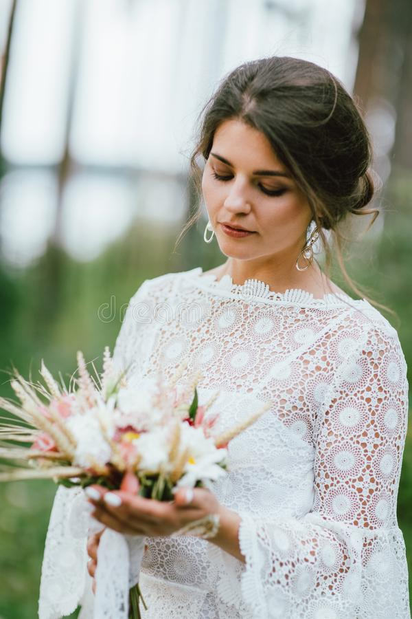 Beautiful smiling bride brunette young woman in white lace dress with wedding boho bouquet, close up portrait outdoors stock image