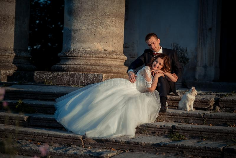 Beautiful smiling bride is leaning on the groom legs while sitting on the old castle stairs with lovely fluffy white cat.  royalty free stock photography
