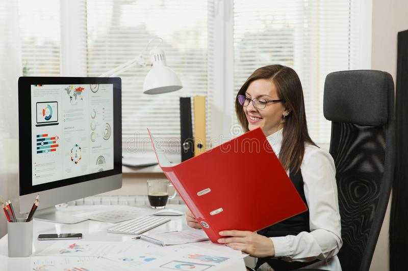 Beautiful business woman in suit and glasses working at computer with documents in light office royalty free stock photography