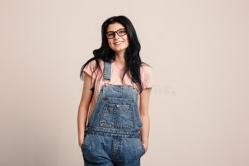 Beautiful smiling brunette girl wearing glasses in denim overall posing beside blank wall. stock image