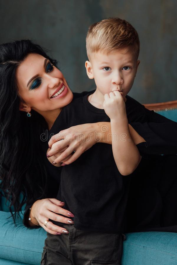 Beautiful brunette mom hugging her son lying on the sofa. Family. mother and her cute boy. black clothes. royalty free stock photos