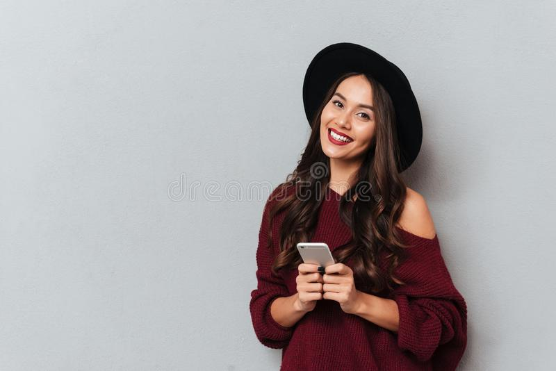 Beautiful smiling brunette woman in black hat holding mobile phone and looking at camera stock images