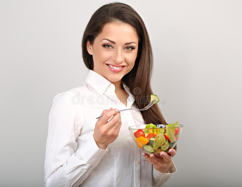 Beautiful smiling business woman eating healthy organic vegetable salad. On the lunch on blue background with empty copy space. Healthy food at work time royalty free stock image