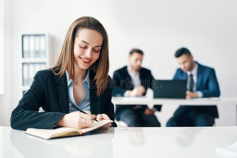 Beautiful smiling business woman writing and making notes in notebook in modern office stock photography