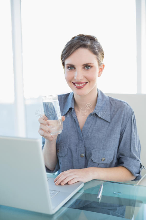 Beautiful smiling businesswoman holding a glass of water sitting at her desk royalty free stock image