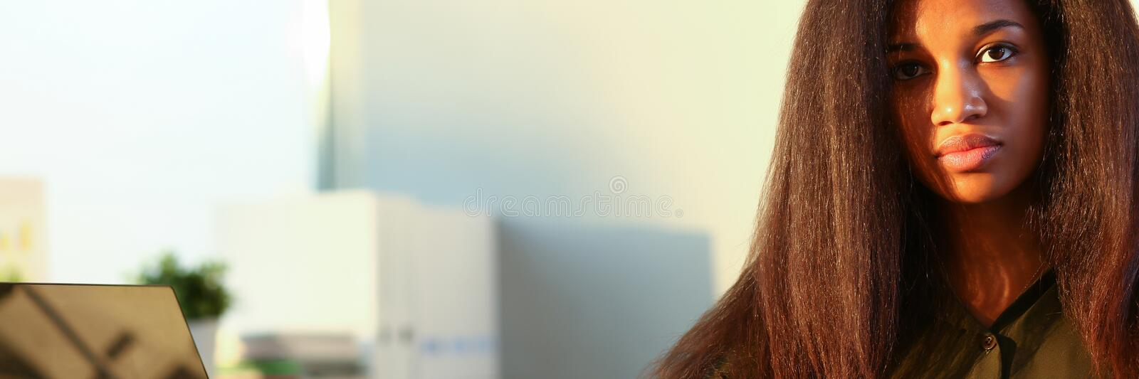 Beautiful smiling businesswoman portrait workplace. Beautiful black smiling businesswoman portrait at workplace look in camera. White collar worker at workspace royalty free stock photo