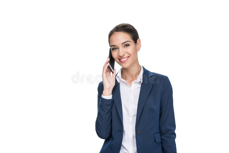 Beautiful smiling businesswoman in suit using smartphone,. Isolated on white stock photography